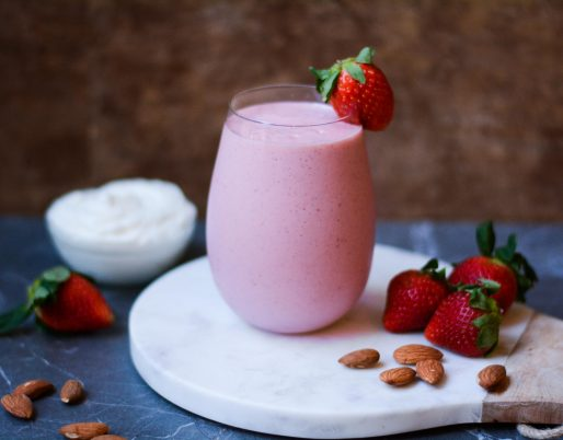 smoothie in glass with strawberries and almonds