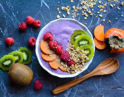 smoothie in a bowl with cut fruit and spoon