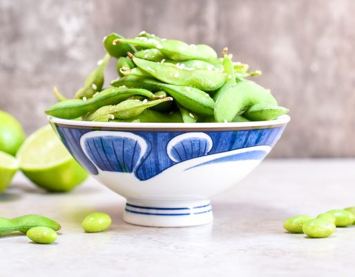 edamame in a blue bowl with limes